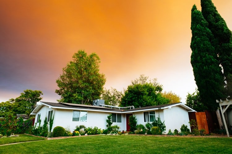 a small and cozy house with a lawn under a pink-orange sky
